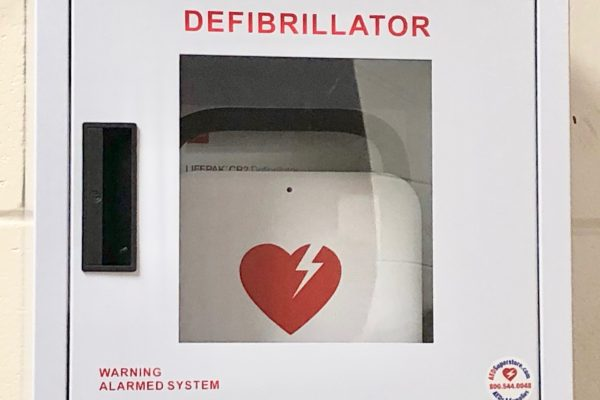 Defigrillator hangins on wall -- white box with red letters and red heart