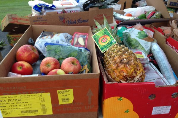 Boxes of fresh fruit and vegetables, including apples and pineapples.