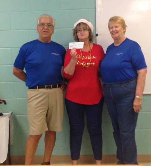 Woman in red handing check to Pantry directors