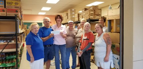 Group of women handing check to Pantry director.