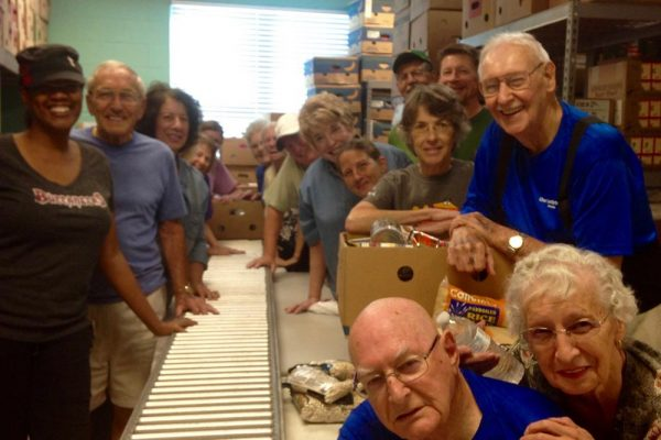 More than a dozen men and women volunteers packing boxes of food for the poor.