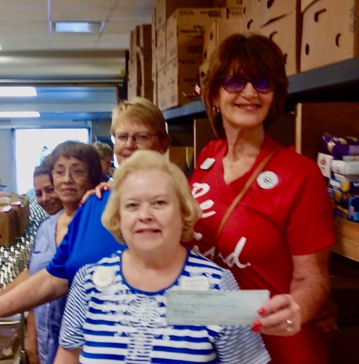 Woman in red shirt donating a check to pantry. Boxes of food in the back.