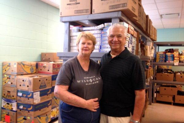 Man and woman in front of hundreds of cartons filled with food.