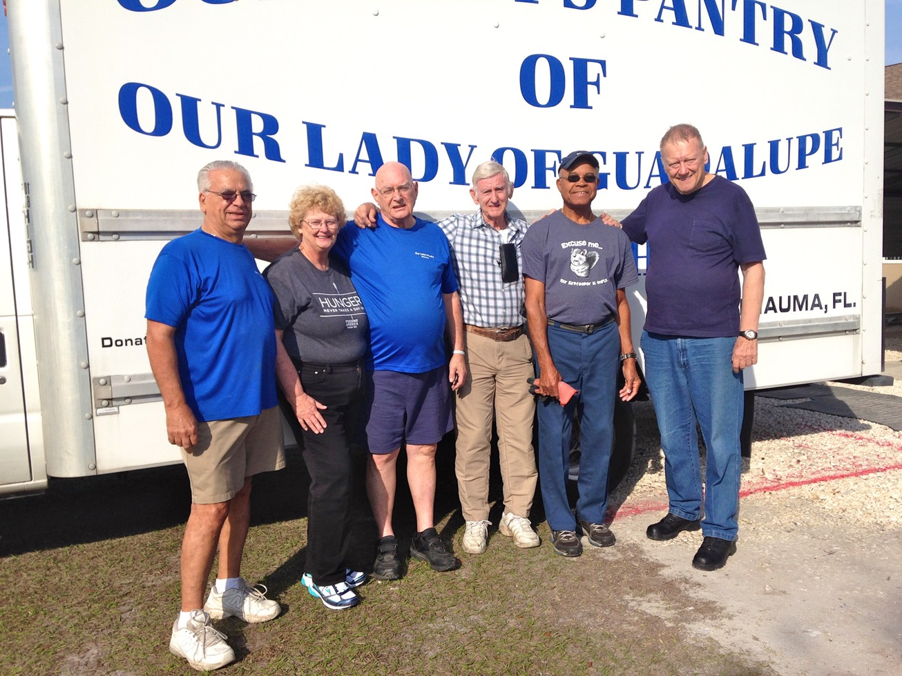Six volunteers standing in front of pantry truck