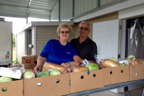 Man and woman in front of boxes of melons, bread, and other produce.