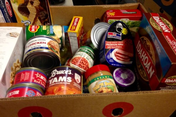 Box of canned goods including tuna, yams, spam, and boxed mashed potatoes.