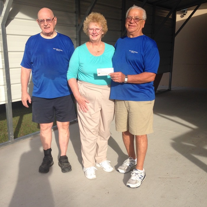 Two men and a woman holding donated check.