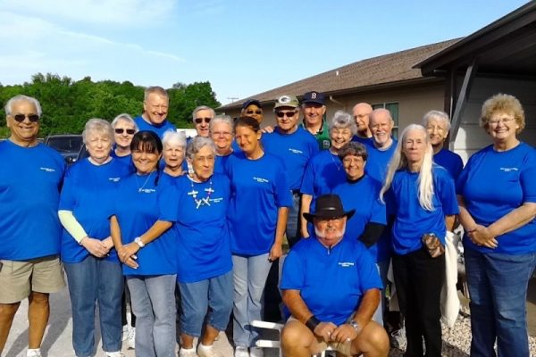 Twenty persons posing -- all in blue Pantry shirts.