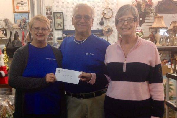 Woman handing donation check to Pantry directors.