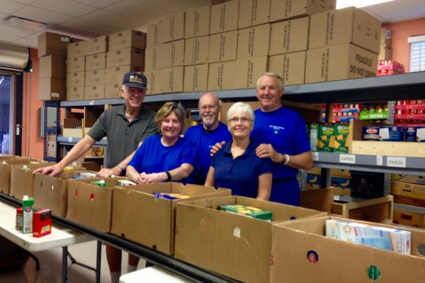 Five men and women volunteers behind boxes filled with food to distribute. More boxes stacked to the ceiling in the back.