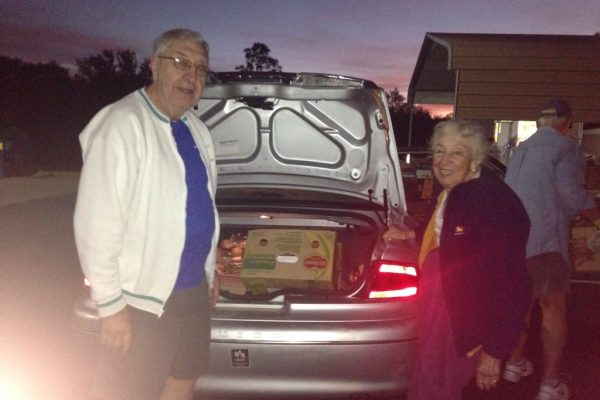 Man and woman unpacking a car full of bread.