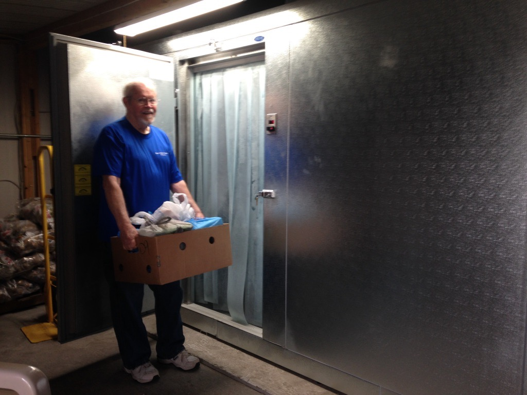 Man carrying refrigerated items in a box to a large freezer