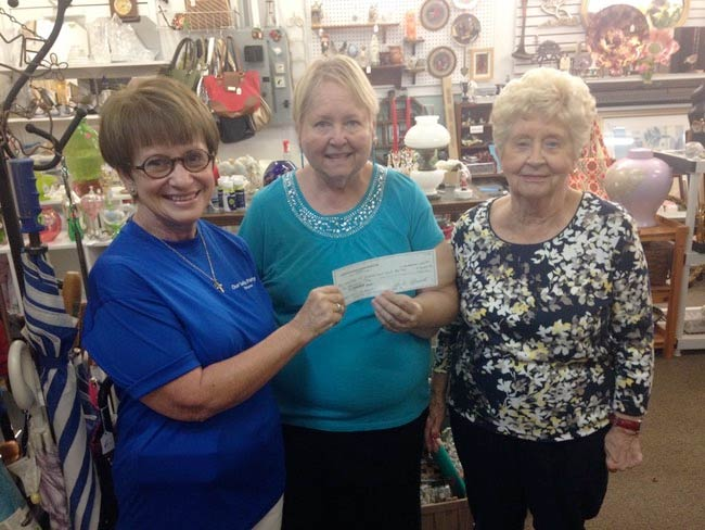 Three women holding a check donated to the Pantry.