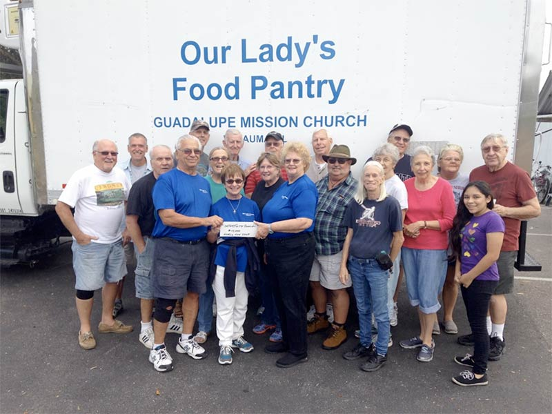 Group in front of pantry truck holding a small check for $10,000 from The Interfaith Council