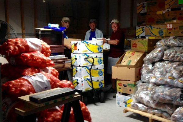 Three men in back room with 50 pound bags of produce