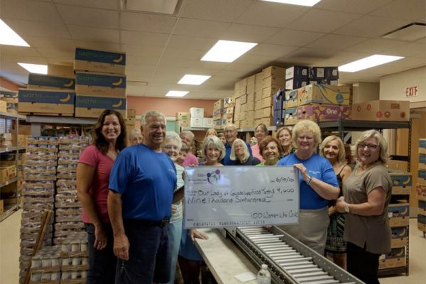 Pantry volunteers and benefactors holding giant donated check.