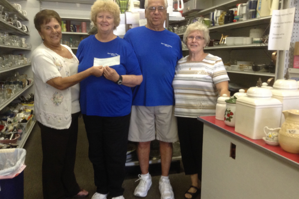 Tom and Anita receiving a check from 2 women.