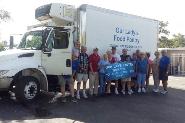 Men and women volunteers in front of a large white truck holding a thank you sign.