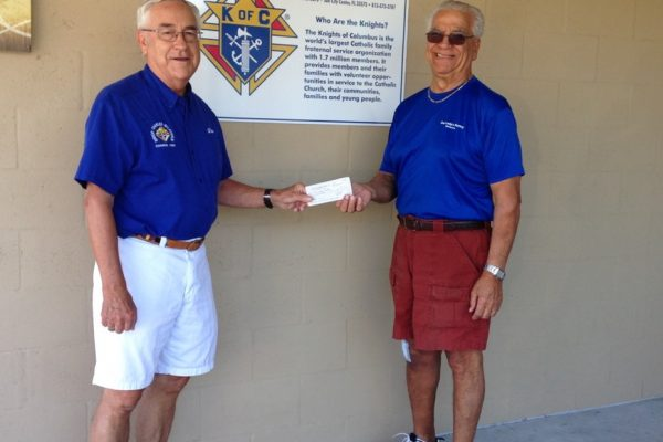 One man handing check to another.  Both in blue shirts.