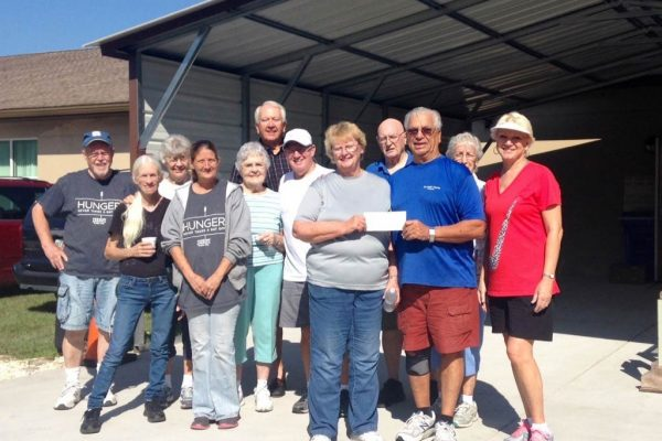 A dozen men and women volunteers posing with a donated check.