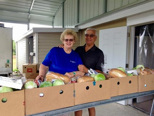 Pantry directors smiling outside in front of boxes of produce