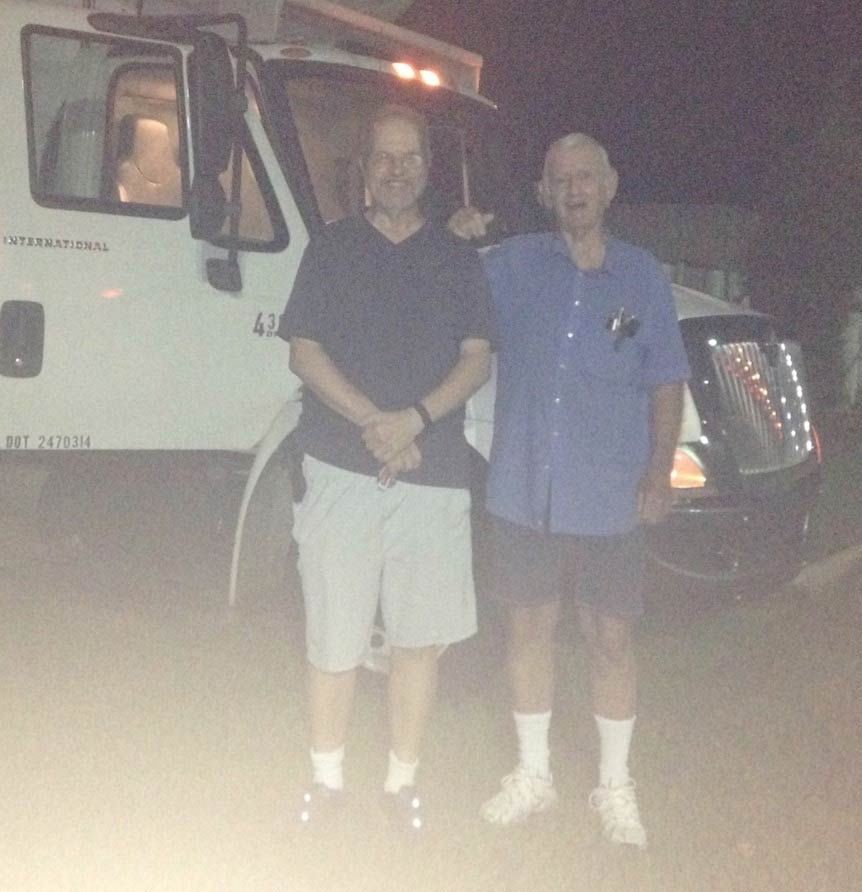 Two men standing in front of Pantry truck before dawn one morning.
