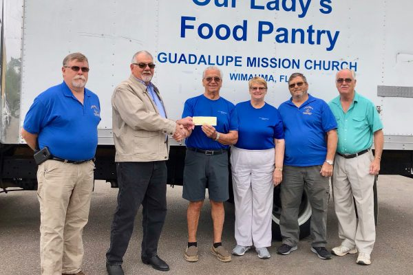 Five men and a woman in front of white pantry truck.