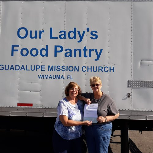 Two women standing in front of Our Lady's Pantry truck