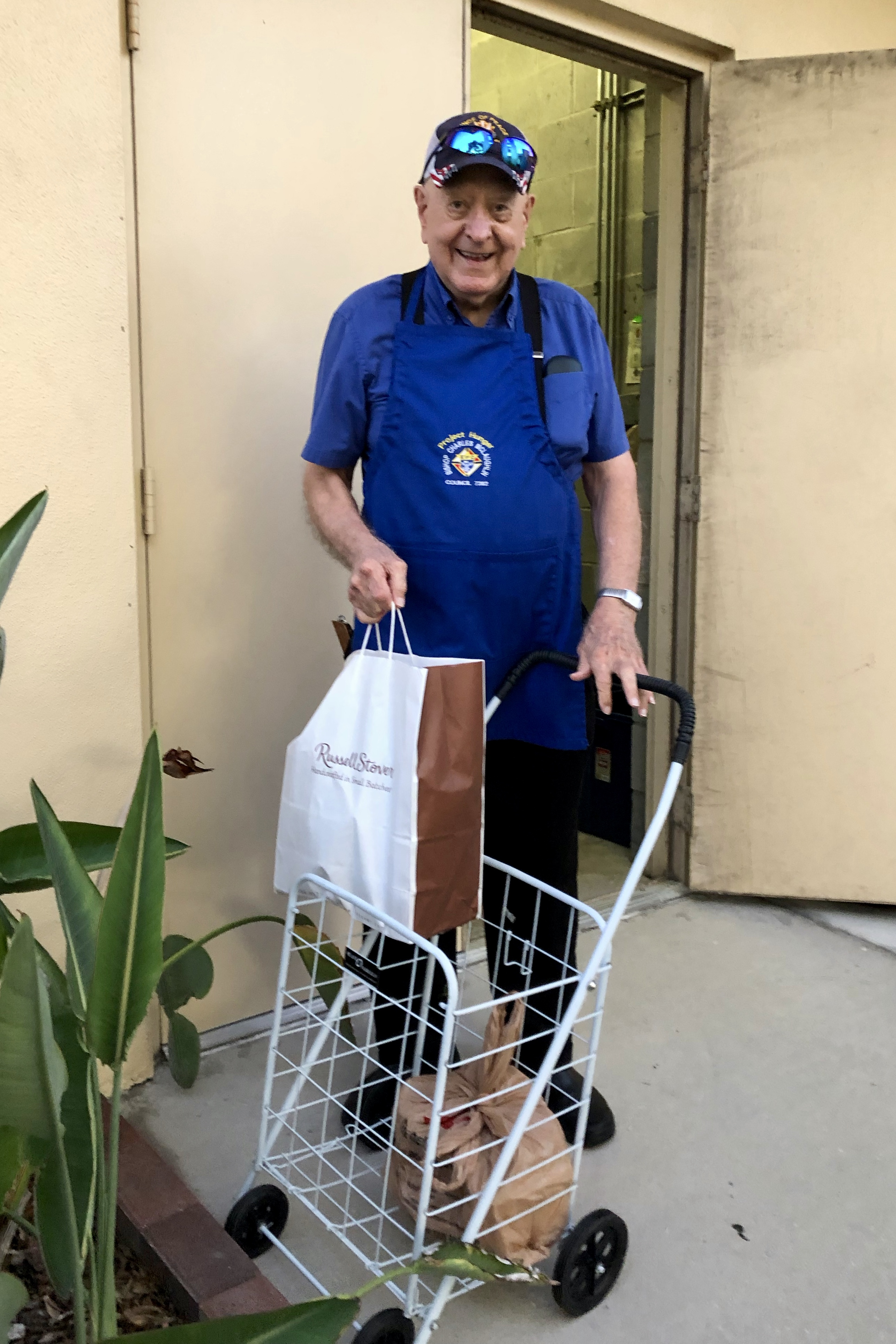 Man in blue shirt lugging a cart full of food donations