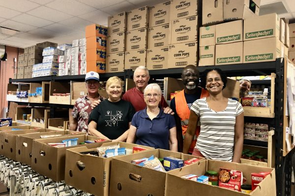 Three couples stand behind dozens of boxes of food being packed for the poor