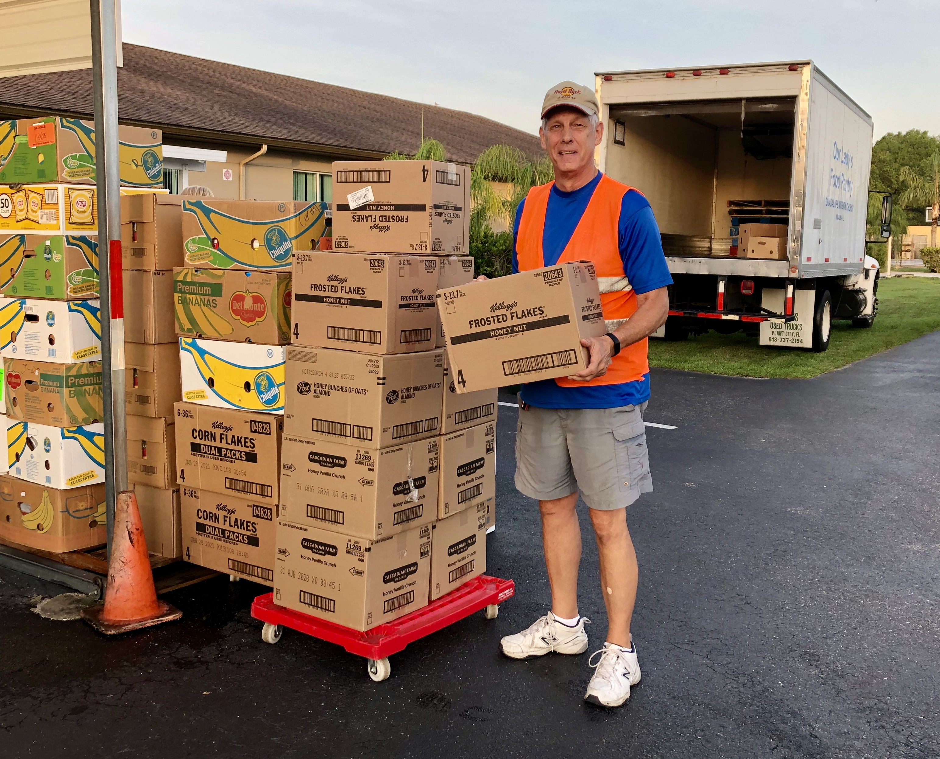 Man holding big box of food, pantry truck in background