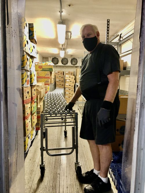 Man with a mask pulling conveyor rollers out of a cooler