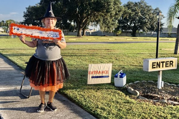 Woman dressed as witch announcing food drive