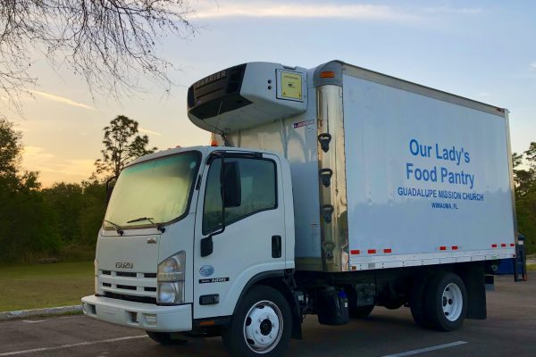 White truck with blue lettering.  Our Lady's Pantry