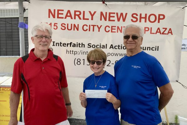 Gentleman in red shirt hands a woman and man in blue shirt a check