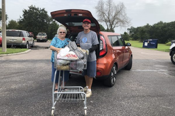 Woman and man unpacking a trunk full of food.  Putting it in a shopping cart.